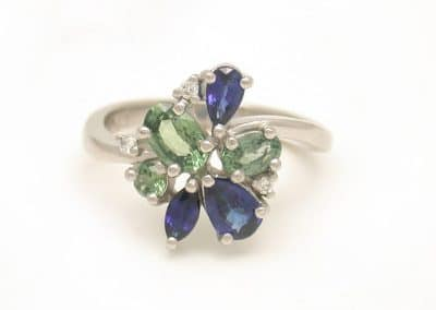 white gold ring with cluster of blue and green sapphires